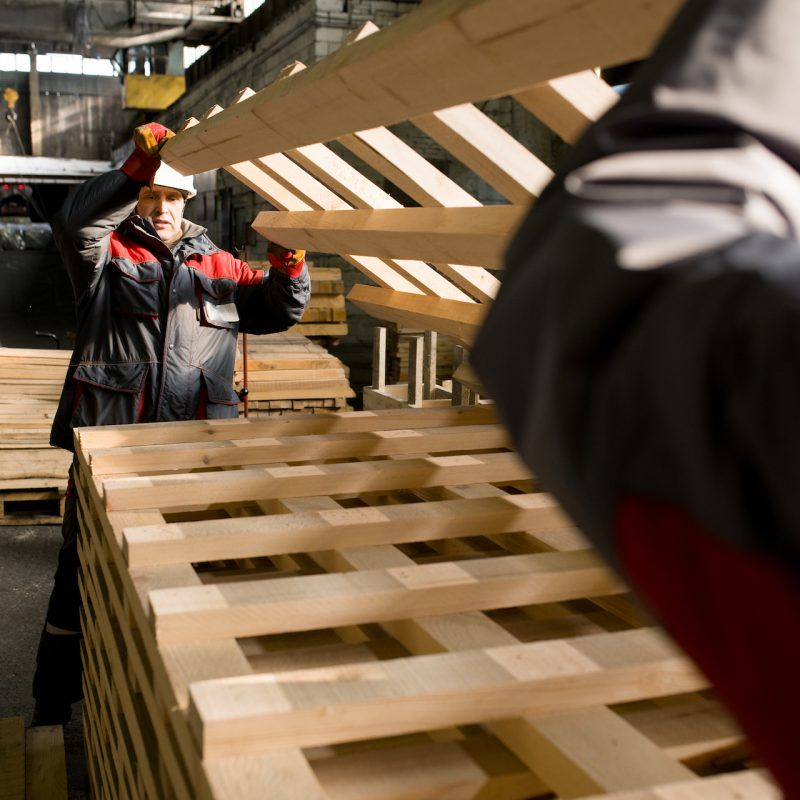 Portrait of two factory workers moving materials in workshop, copy space